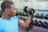 Young muscular man exercising with dumbbell in the gym