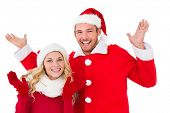 Festive couple smiling with arms raised on white background