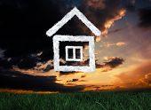 Cloud house against green grass under dark blue and orange sky