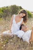 Relaxed young couple sitting on countryside landscape