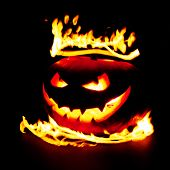 Scary smiling halloween pumpkin in flames on black background