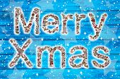 Merry Xmas Wishes On Blue Wooden Background And Collage.