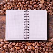 Pure Notebook For Menu, Recipe Record On Wooden Table Top View. Coffee Beans As Background