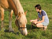 Horse grazing, with a pretty girl watching him and holding the lead rope