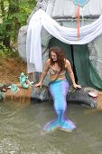 MUSKOGEE, OK - MAY 24: A woman dressed as a fairy mermaid shares treasures and smiles with kids at O