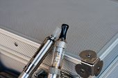 foto of sensory perception  - Two electronic cigarettes on silver metal briefcase - JPG