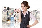 Confident Asian business woman give you a okay sign standing in front of TV screen wall, closeup por