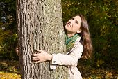 Happy Young Woman In Autumn Embrassing A Tree.