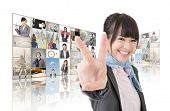 Confident Asian business woman give you a victory sign and standing in front of TV screen wall, clos