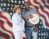 A mature western couple giving tribute to their country.  They're against a backdrop of a large American flag.