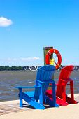 Two wooden chairs and lifebuoy on the pier overlooking Woodrow Wilson bridge.