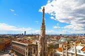 A statue of the Dome of Milan cathedral with the city view in summer.