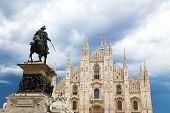 Milan Cathedral Dome with statue against a cloudy sky in summer.