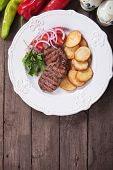 Grilled beef steak with roasted potato and tomato salad
