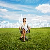 smiley young businesswoman sitting on the chair at green field against drawing city