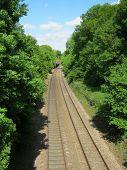 Train tracks leading off into the distance towards a blue sky.