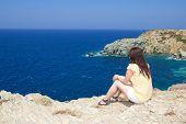 Woman Sitting On Rocky Cliff On Sea Coast
