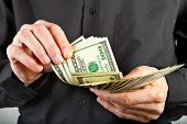 Man Counts Money In Hands