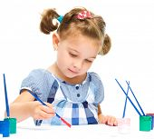 Little girl is painting with gouache while sitting at table, isolated over white