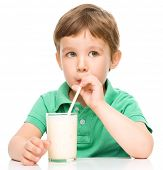 Cute little boy drinks milk using a drinking straw, isolated over white