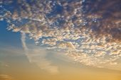 Small Clouds In Dark Yellow And Blue Sunset Sky