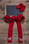 Chalk Board With Red Knitted Sock And Bow On Wooden Background For Birth