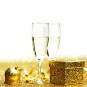 Champagne in glasses and gift box on golden background