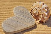 stock photo of heartfelt  - Wooden Heart and Sea Shell on a Beach Sand Summer Marine Background with space for text or image