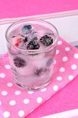 Cold cocktail with forest berries, frozen in ice cubes on bright background