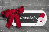 Red Bow On Chalk Board With Voucher - Gutschein Message On Snowflake Designgrey Wooden Background -