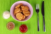 Chicken nuggets with sauces on table close-up