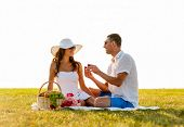 love, dating, people and holidays concept - smiling young man showing small red gift box to his girl