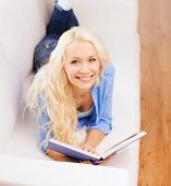 leisure, reading and home concept - smiling middle-aged woman reading book and lying on couch at hom