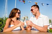 love, dating, people and holidays concept - smiling couple wearing sunglasses drinking champagne and