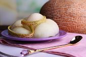 Melon in plate on napkin on cutting board on wooden table on natural background
