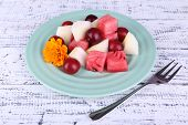 Slices of melon, plum and watermelon in plate on wooden background