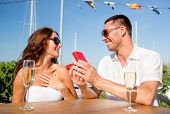 love, dating, people and holidays concept - smiling couple wearing sunglasses with champagne and red