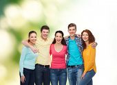 friendship, ecology and people concept - group of smiling teenagers standing and hugging over green