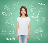 advertising, school, education, childhood and people - smiling little girl in white blank t-shirt ov