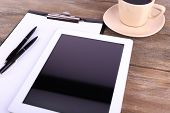 Tablet, cup of coffee, pens and folder with paper on wooden background