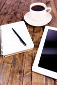 Tablet, cup of coffee, notebook and pen on wooden background