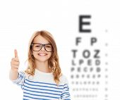 education, school and vision concept - smiling cute little girl with black eyeglasses showing thumbs