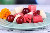 Slices of melon, plum and watermelon in plate on wooden table on natural background