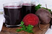 Glasses of fresh beet juice and vegetables on cutting board on wooden background