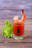 Fresh boiled prawns with lettuce in a glass with tomato sauce on wooden background