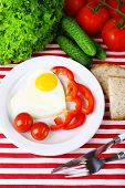 Scrambled eggs with vegetables served on plate on fabric background
