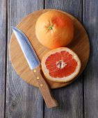 Ripe grapefruits and knife on cutting board, on wooden background