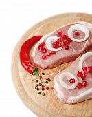 Raw meat steak with, spices, onion rings on cutting board, isolated on white