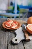 Ripe grapefruits and knife on cutting board, on wooden table, on bright background