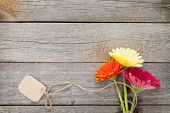 Three colorful gerbera flowers with tag on wooden table